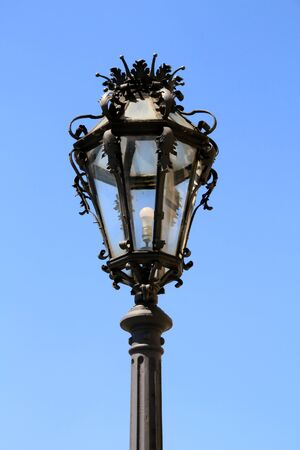old cast-iron street lamp against blue sky in Vienna