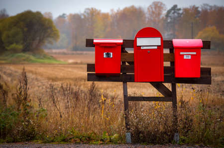Three red mailboxes in the countryside near an autumn field