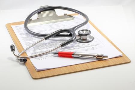 historia clinica: portapapeles informe m�dico con la pluma estereoscopio en el fondo blanco