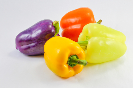 capsicum: Green Orange Yellow Violet Capsicum Bell Pepper on white background