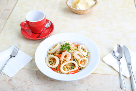 pasta: Seafood spaghetti prawn squid on table with utensils and cup