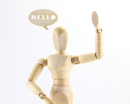 marioneta de madera: Figura de madera de marionetas con el signo de la palabra HOLA en el fondo blanco