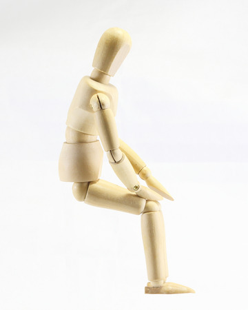 marioneta de madera: marioneta expresión ubicación pensamiento madera mirar hacia abajo en el fondo blanco Foto de archivo