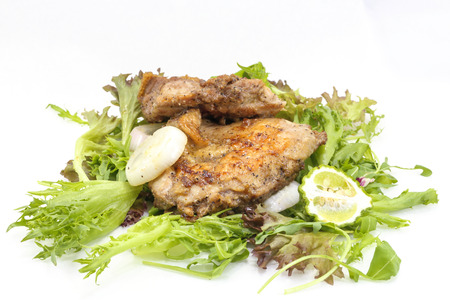 Alla griglia Cosce di pollo con insalata verde su sfondo bianco Archivio Fotografico