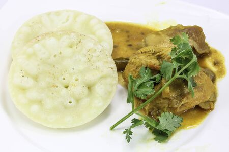 bengali: Rice flower Chitoi Pitha traditional Bengali pancakes with chicken curry Stock Photo