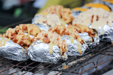 grilled potato: Baked Grilled Potato with stuffing cheese toping charcoal flame grill at farmer market stall