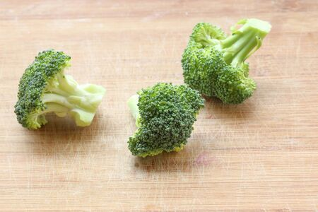 brocoli: Green broccoli cut sliced chopped on wooden chopping board Stock Photo