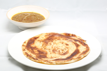 ghee: Plain Ghee Fried Paratha with curry dal on plate and bowl white background