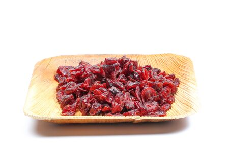 cranberry fruit: Dried Cranberry Fruit tasty healthy berry on white background in a palm leaf plate Stock Photo