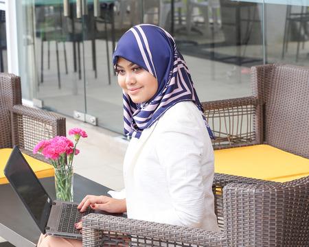 Asian Muslim woman headscarf sitting outdoor laptop work Stock Photo