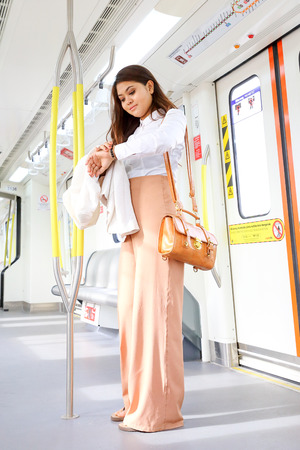 Asian young woman in train transport stand watch time