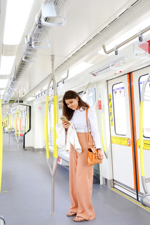 work worker: Asian young woman in train transport stand use smartphone