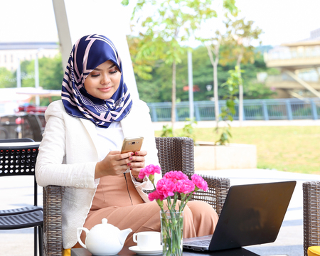Asian Muslim woman headscarf sitting outdoor computer smartphone text look Imagens