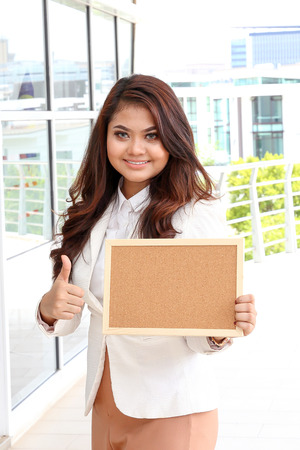thumps up: Asian young woman smile holding blank board space thumps up