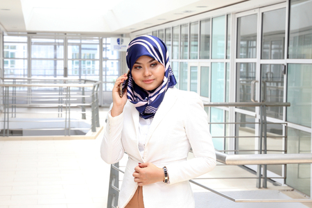 head scarf: Asian young Muslim Woman talking texting smart phone head scarf Stock Photo
