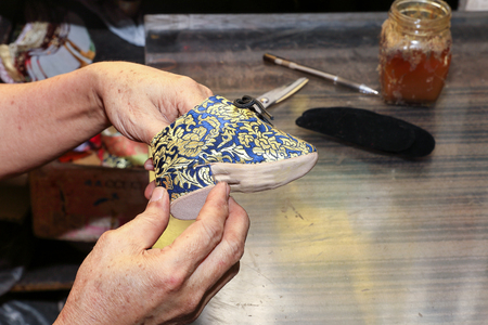 bounded: Bounded feet lotus mini traditional shoe crafts making Stock Photo