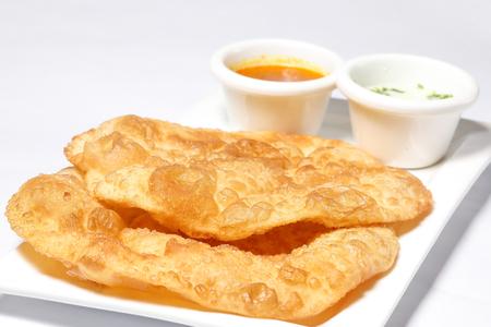 puri: Deep Fried Puri Luchi with gravy raita one white plate Stock Photo