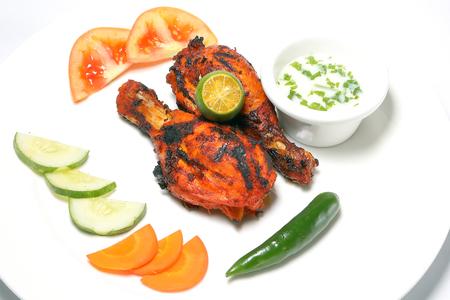 Grilled Chicken tandoori spicy hot drumsticks with salad and raita