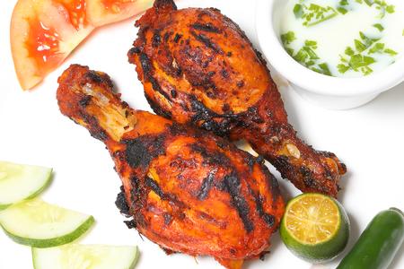 Grilled Chicken tandoori spicy hot drumsticks with salad and raita Stock Photo - 77833879