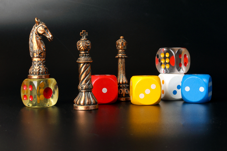 Colourful playing gaming dice transparent metal chess pieces on black background