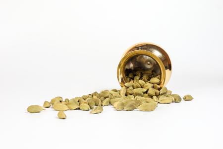 Cardamom  spice in shiny metal pot brass copper golden on white background