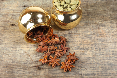 mix spice in golden metal pot on rustic wood background star anise cardamom copper brass