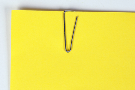 Paper clip holding on blank colour paper text copy space note