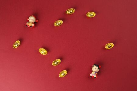 Chinese boy girl doll figurine money syce ingot gold on red background copy space