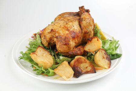Whole roasted grilled chicken poultry bird with baked potato vegetable salad tomato lemon on white background