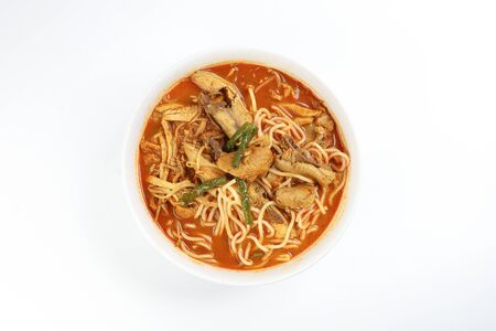 Malaysian curry yellow mee noodle with roasted chicken slice in white bowl on white background