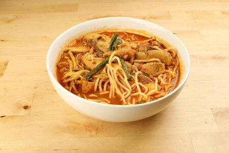 Malaysian curry yellow mee noodle with roasted chicken slice in white bowl on wooden background