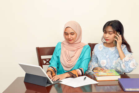 Two young Asian Malay Muslim woman wearing headscarf at home office student sitting at table phone computer book document study talk work mingle