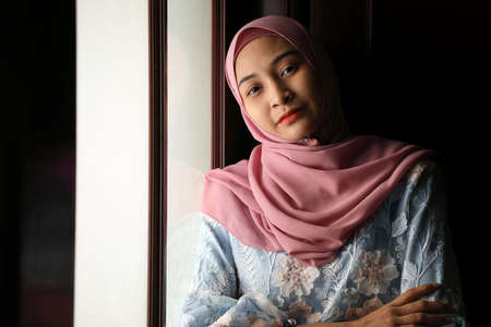 young Asian Malay muslim woman wearing headscarf baju kurung dress at home in front window mood light on face dark background peaceful content calm tranquil break trough wonder happy