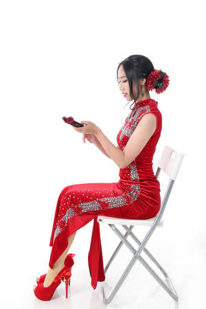 South east Asian Chinese race ethnic origin woman wearing red velvet cheongsam with hand stitched sequence work dress costume hand fan on white background