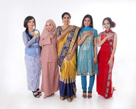 South east Asian Malay Chinese Indian race ethnic origin woman wearing dress costume baju kurung cheongsam samfu kebaya Sharee multiracial community on white background welcome hand on chest