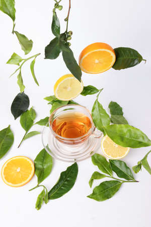 different types of fresh raw green tea leaf flower bud dropping floating elevated lemon orange slice over transparent glass teacup saucer liquid tea on white background top view Stock fotó