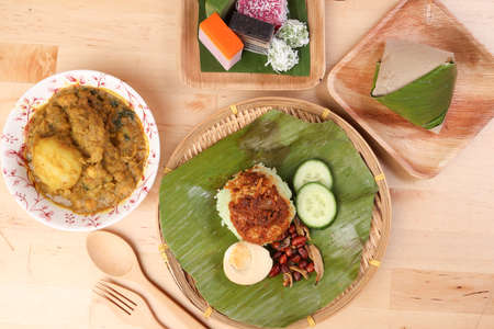 Nasi Lemak fragrant rice coconut milk with sambal friend peanut anchovy egg packed banana leaf round bamboo plate colorful nyonya kuih sweet desert palm leaf plate on wooden background Stock Photo