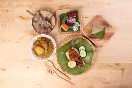 Nasi Lemak fragrant rice coconut milk with sambal friend peanut anchovy egg packed banana leaf round bamboo plate colorful nyonya kuih sweet desert palm leaf plate on wooden background