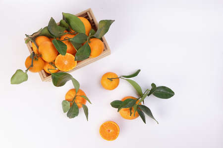 mandarin orange green leaf in wooden box crate top view copy text space on white background
