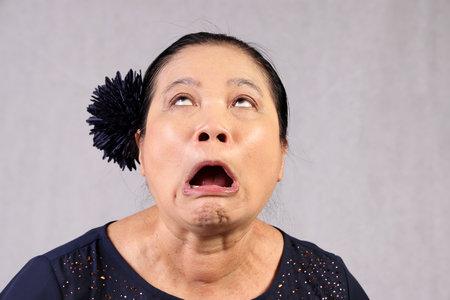 Elderly senor Asian woman posing facial expression disgust shocked mouth open cross eye faint