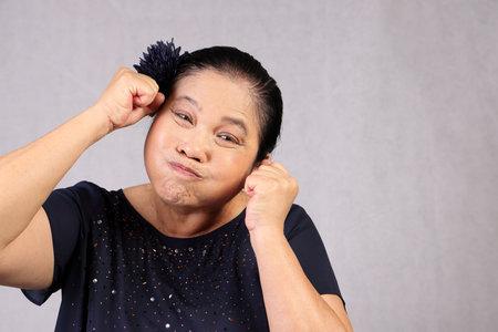 Elderly senor Asian woman posing facial expression funny witty blowing cheek