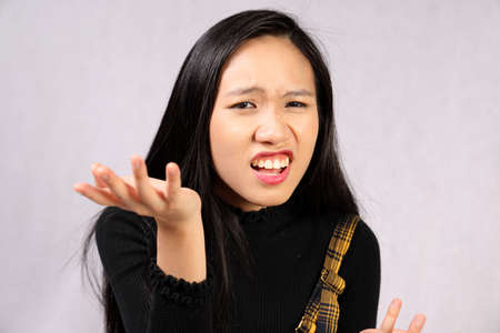 Young attractive southeast Asian woman posing facial expression question crazy hand raised