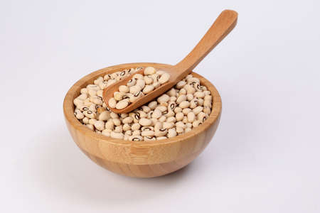 Blackeye beans in wooden bowl scoop spoon on white background