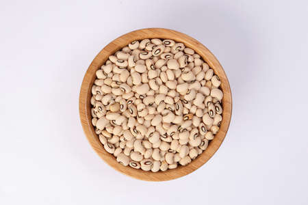 Blackeye beans in wooden bowl top view on white background