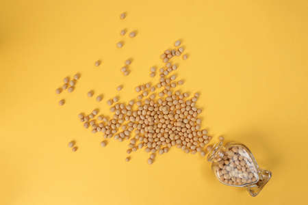 Soyabeans pouring from hart shape glass bottle on yellow background
