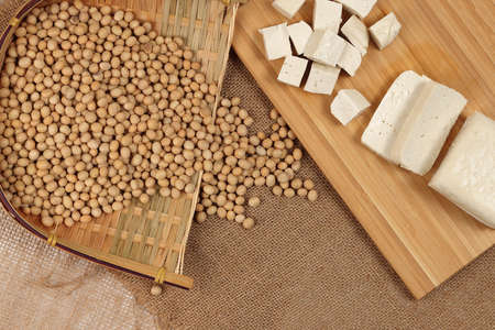 Soyabeans curd tofu soya beans flowing bamboo sieve wooden board on jute background