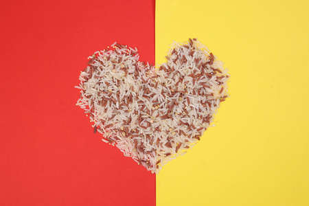 Mixed low glycaemic index healthy rice grain basmati millet buckwheat red rice hart shape on red yellow background