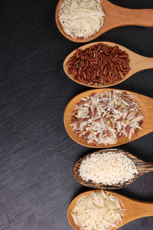 Long grain basmati medium grain jasmine short grain pilaf polau risotto brown low glycaemic index gi rice in wooden spoon on black background copy text space top flat lay view