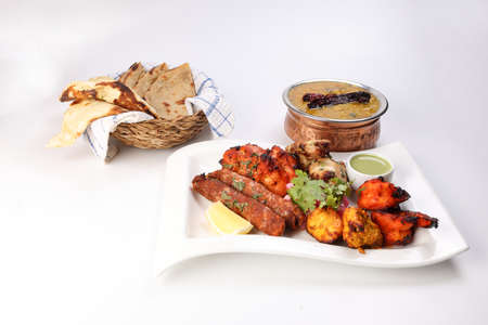 Mixed grill kebab chicken mutton beef prawn fish mint sauce lemon pickled onion bread basket chapati naan tandoori paratha dal lentil fry tadka copper pot on white dish over white background