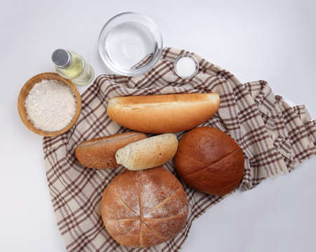 Freshly baked bread loaf bun roll round long mix verity wrapped in checkered kitchen fabric napkin towel wheat flower oil water salt over white background